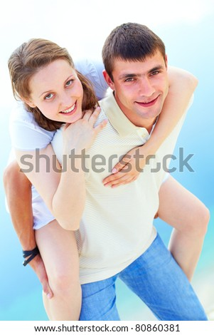 Photo of happy girl embracing her boyfriend and both looking at camera - stock photo