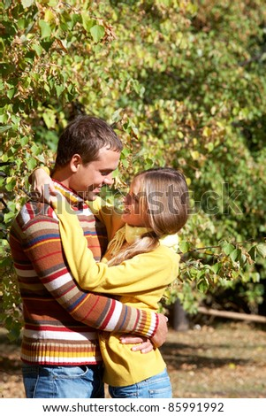 Photo of happy girl embracing her boyfriend outdoors in autumn - stock photo