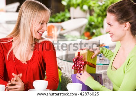 Photo of happy girl putting giftbox into paperbag after showing it to her friend - stock photo