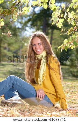 Photo of happy girl seated on ground in park in autumn - stock photo