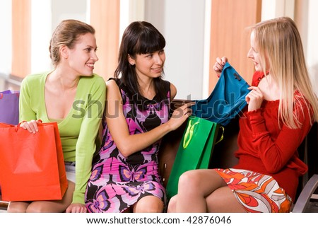 Photo of happy girl showing fashionable blouse to her friends