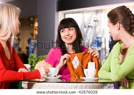 Photo of happy girl showing fashionable pullover to her friends in cafe - stock photo