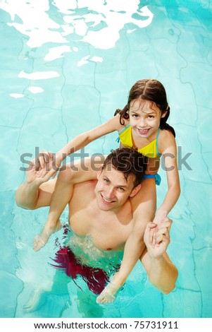Photo of happy girl sitting on her father shoulders in pool - stock photo