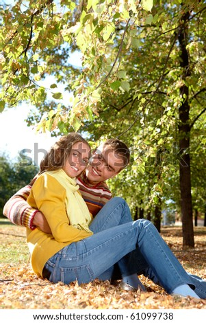 Photo of happy girl with handsome male relaxing in park - stock photo