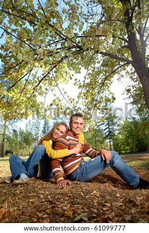 Photo of happy girl with handsome male relaxing outdoors in autumn - stock photo