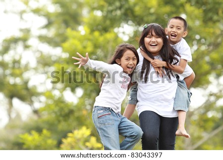 Photo of happy girls and boy having fun in green nature