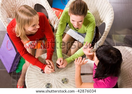 Photo of happy girls chatting in cafe after shopping - stock photo
