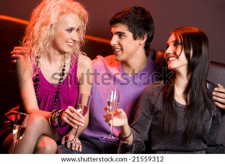 Photo of happy guy between two pretty girls chatting at xmas party
