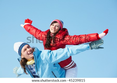 Photo of happy guy giving piggyback to joyful girl during winter vacation - stock photo