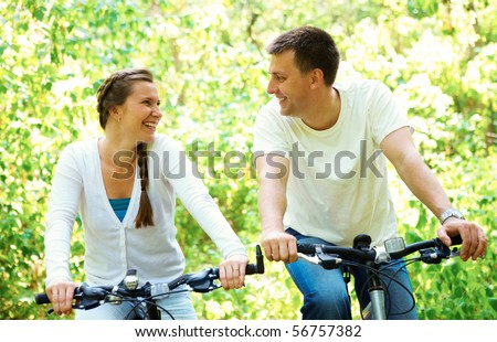 Photo of happy husband and wife laughing while riding bicycles in park - stock photo