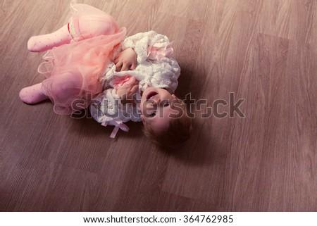 photo of Happy little girl lying on the floor - stock photo