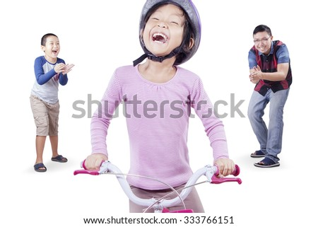 Photo of happy little girl wearing helmet and try to ride a bicycle with her family on the back, isolated on white background - stock photo