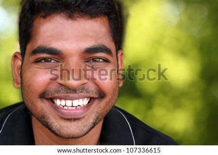 Photo of happy lively handsome middle-aged Indian/asian youth laughing and having fun. The eyebrows are thick and prominent and hair is black and curly with unshaven stubble on the face. - stock photo