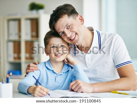 Photo of happy man and his son looking at camera - stock photo