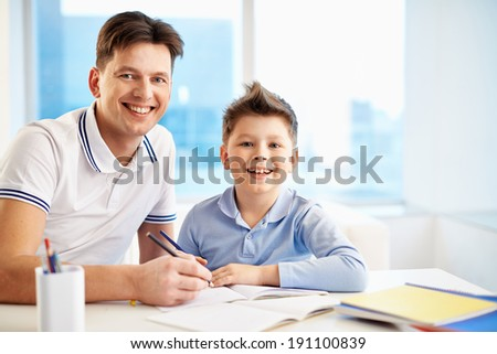 Photo of happy man and his son sitting by table and looking at camera while drawing - stock photo