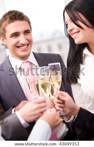 Photo of happy man and woman holding flutes with champagne and smiling while toasting at party