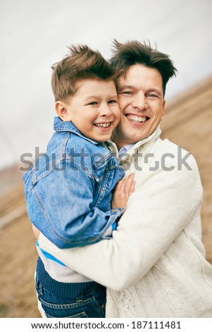 Photo of happy man embracing his son and looking at camera - stock photo