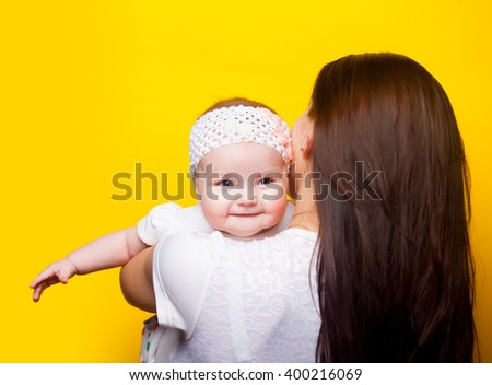 photo of happy mother and daughter on the yellow background