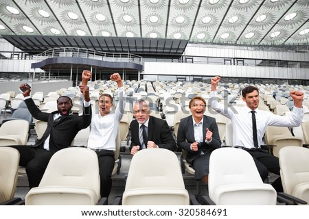 Photo of happy multi ethnic business people. Mixed race business team sitting in row and cheering on modern sport stadium. Stadium seats as a background - stock photo