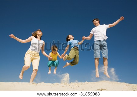 Photo of happy parents holding their son by hands in jump with bright blue sky at background - stock photo