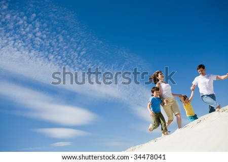Photo of happy parents holding their sons by hands and running down sandy shore with bright blue sky at background - stock photo