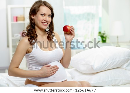 Photo of happy pregnant woman with ripe apple looking at camera - stock photo