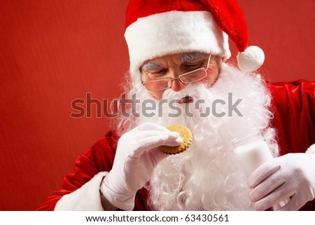 Photo of happy Santa Claus with glass of milk looking at biscuit in his hand - stock photo