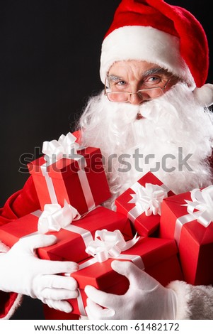 Photo of happy Santa Claus with red giftboxes looking at camera - stock photo