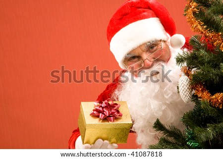 Photo of happy Santa Claus with small giftbox looking at camera out of decorated xmas tree - stock photo