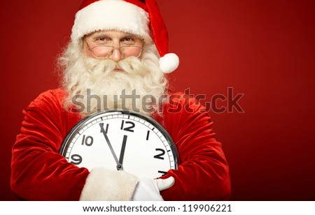Photo of happy Santa holding clock showing five minutes to midnight - stock photo
