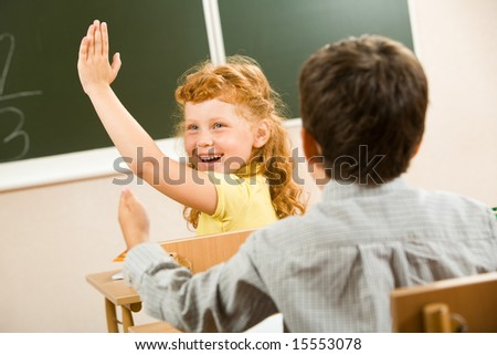 Photo of happy schoolgirl sitting and raising her hand at the lesson - stock photo