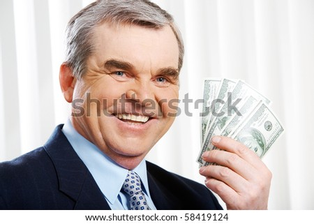 Photo of happy senior businessman showing dollar banknotes - stock photo