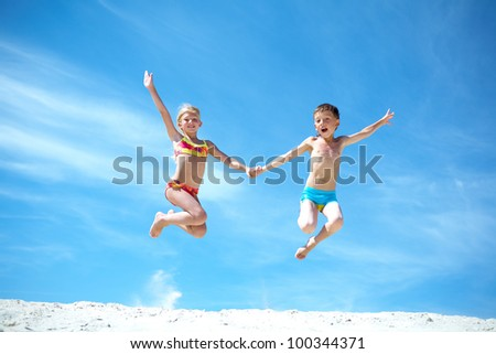 Photo of happy siblings jumping over sand and looking at camera - stock photo
