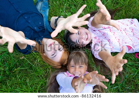 Photo of happy three girls lying on green grass - stock photo