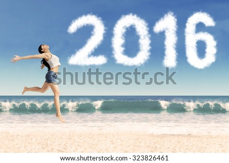 Photo of happy woman enjoy freedom on the beach while dancing on the sand with cloud shaped numbers 2016 - stock photo