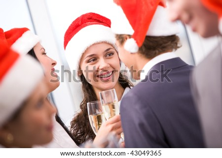 Photo of happy woman in santa cap holding flute with champagne and smiling at her colleagues during party - stock photo