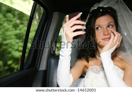 Photo of happy woman in wedding dress looking at the mirror