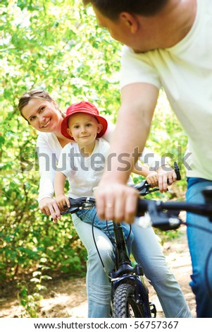 Photo of happy woman with son riding a bicycle in park while looking at her husband - stock photo