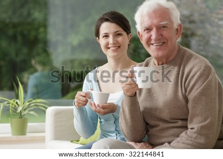 Photo of happy young caregiver and elderly male drinking coffee - stock photo