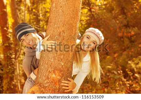 Photo of happy young family having fun in autumnal woods, closeup portrait of cute cheerful couple peeking from behind a tree outdoors, beautiful golden autumn season, love concept - stock photo