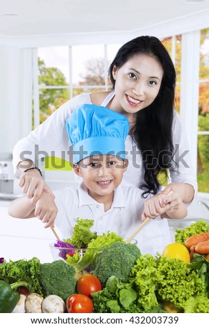 Photo of happy young mother and her son cooking vegetables salad together in the kitchen - stock photo