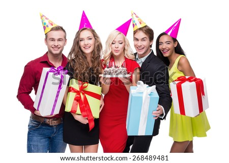 Photo of happy young people standing isolated on white background. They wearing birthday hats and holding colourful presents. Blonde woman holding cake with candles. Concept for happy birthday - stock photo