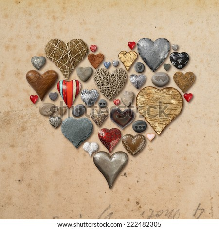 Photo of heart-shaped things made of stone, metal and wood organized in the shape of a heart over vintage paper background. - stock photo