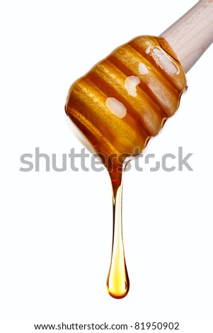 Photo of Honey dripping from a wooden dipper isolated on a white background. - stock photo