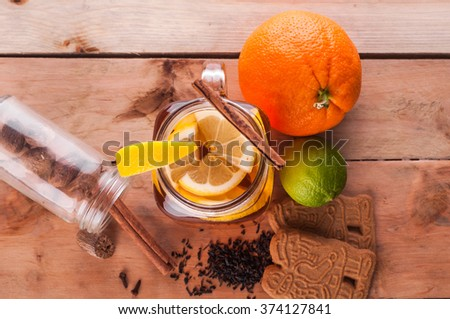 Photo of Hot spiced tea in jar on wooden table - stock photo