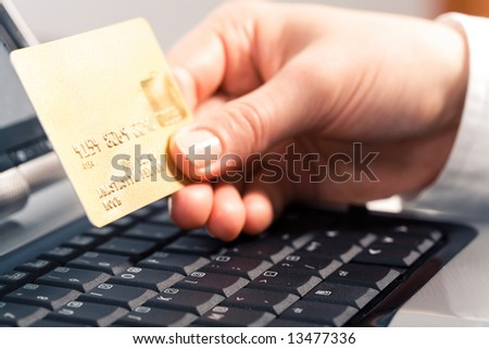 Photo of human hand holding the credit cart over black keyboard - stock photo