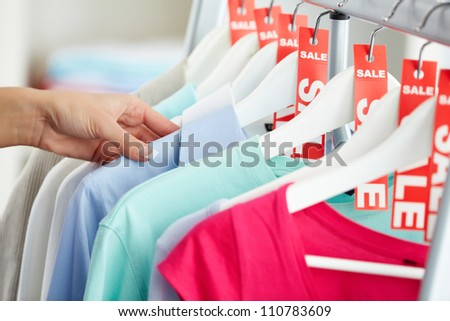 Photo of human hand searching through hangers with clothes - stock photo