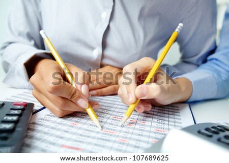 Photo of human hands holding pencils and pointing at numbers in documents - stock photo