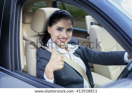 Photo of Indian female entrepreneur showing thumb up while driving a new car on the road