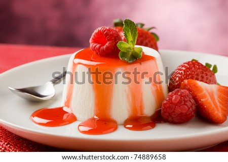 photo of italian panna cotta dessert with strawberry sirup and mint leaf - stock photo